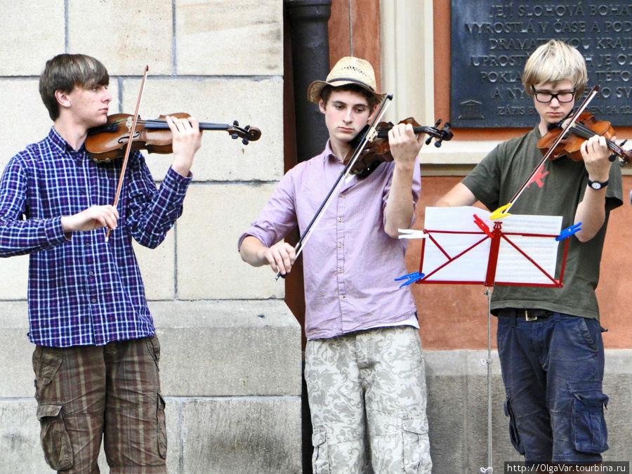 Трио молодых скрипачей исполняло что-то классическое без особого энтузиазма