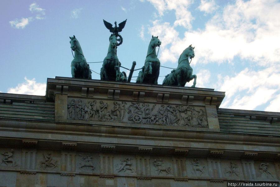 Над воротами возвышается знаменитая и часто фотографируемая Квадрига работы Готфрида Шадова, построенная в 1793 г, на которой изображена статуя богини Мира Айрене, правящая колесницей, запряженной четырьмя конями