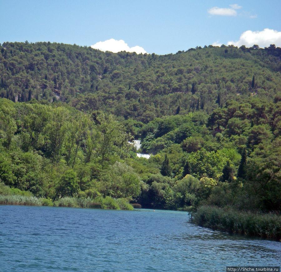 вот вдалеке река как бы заканчивается горой, а среди листвы виднеется каскад водопада...