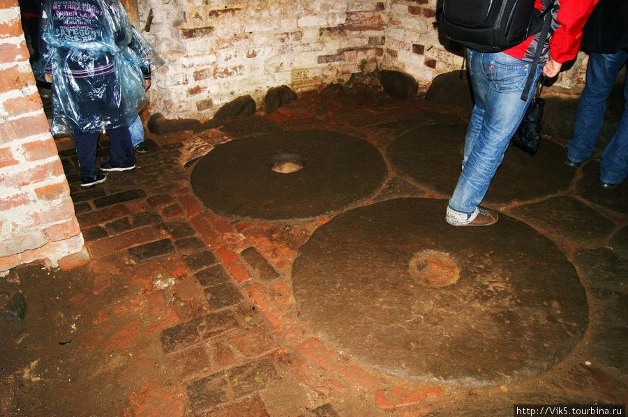 Старые жернова от мельницы использовали как отмостка пола.