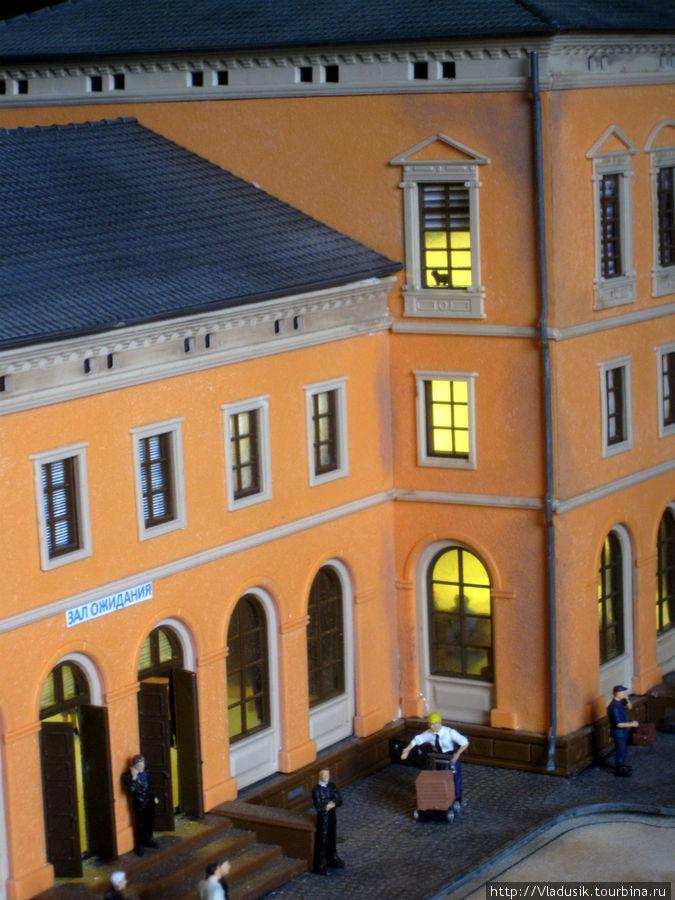 Внутри здания вокзала сидят люди на чемоданах, соседний вход — это ресторан, там едят за столиками и танцуют. Котэ на верхнем этаже наблюдает.