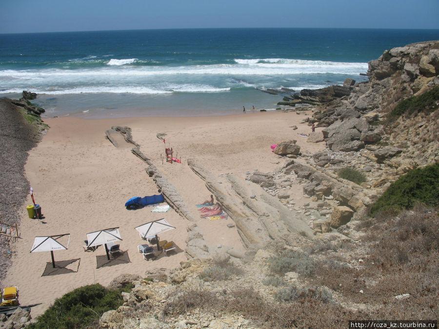 вид сверху на пляж, есть несколько зонтов и лежаков, кроме того есть бар и кресла-подушки под навесом. Спуск на пляж по ступенькам