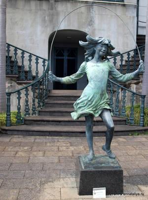 Скульптура девочки перед дворцом.