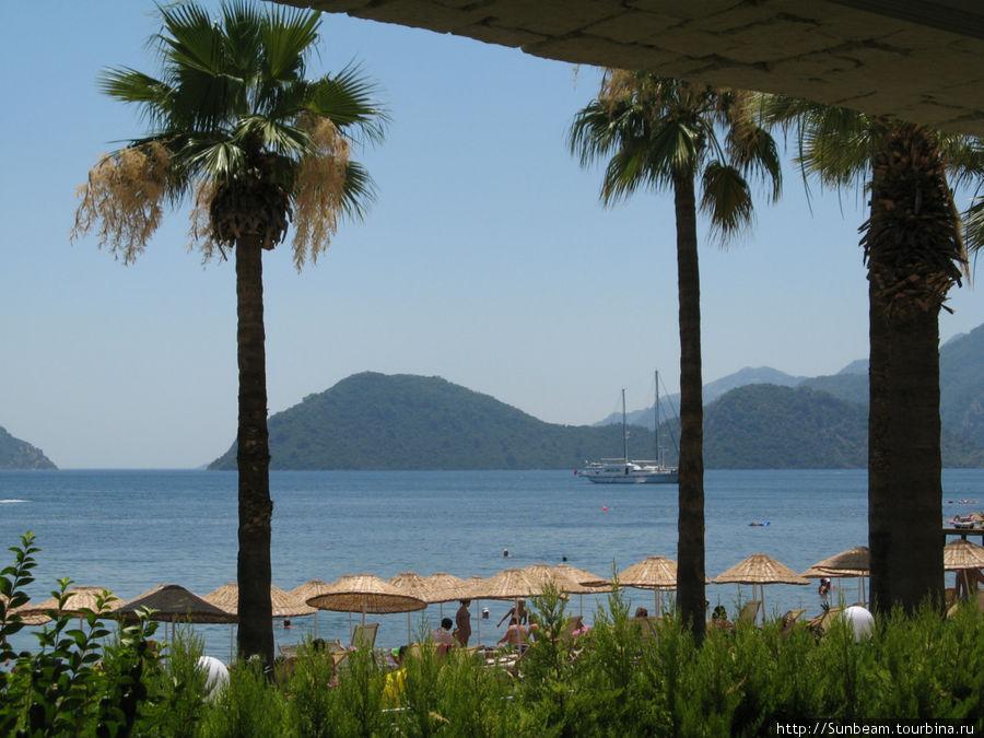 Вид на море из кондитерской отеля, где можно попить чая или кофе со всяким сладостями. Зонтики — с пляжа отеля Ideal Prime Beach.