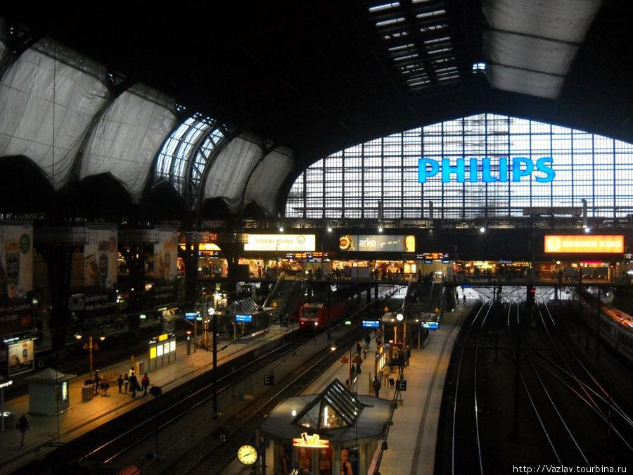 Платформы и пути; вдалеке видны помещения магазинов и кафе, вознесённые на галерею