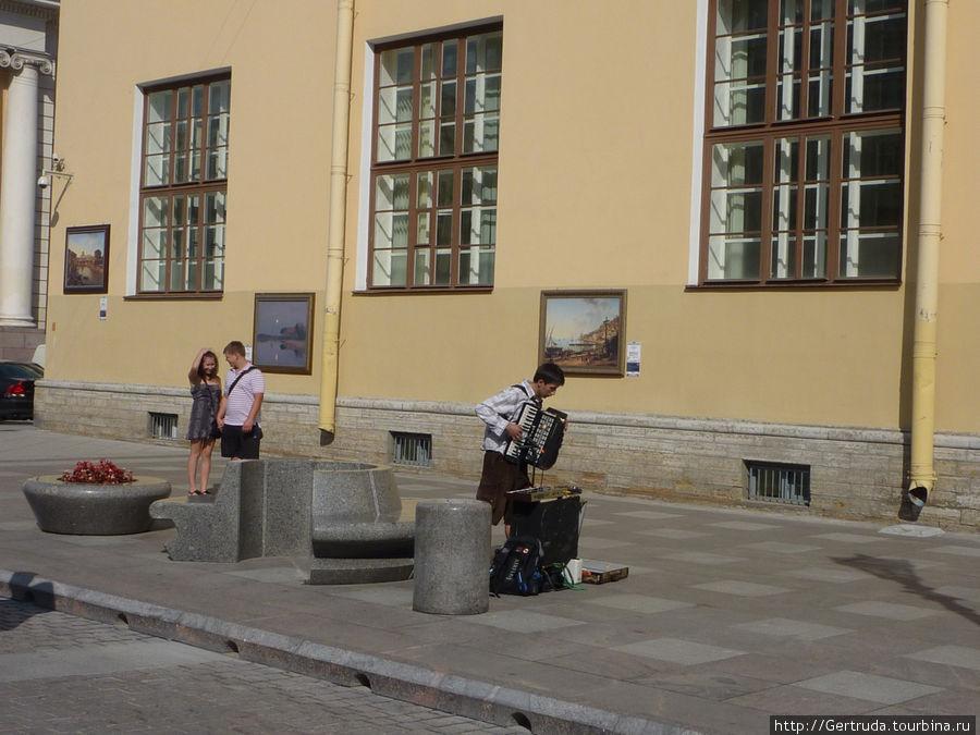 Картины на стене здания и очередной музыкант.