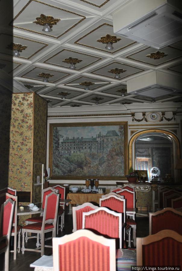 В зале для завтраков картины и зеркала.