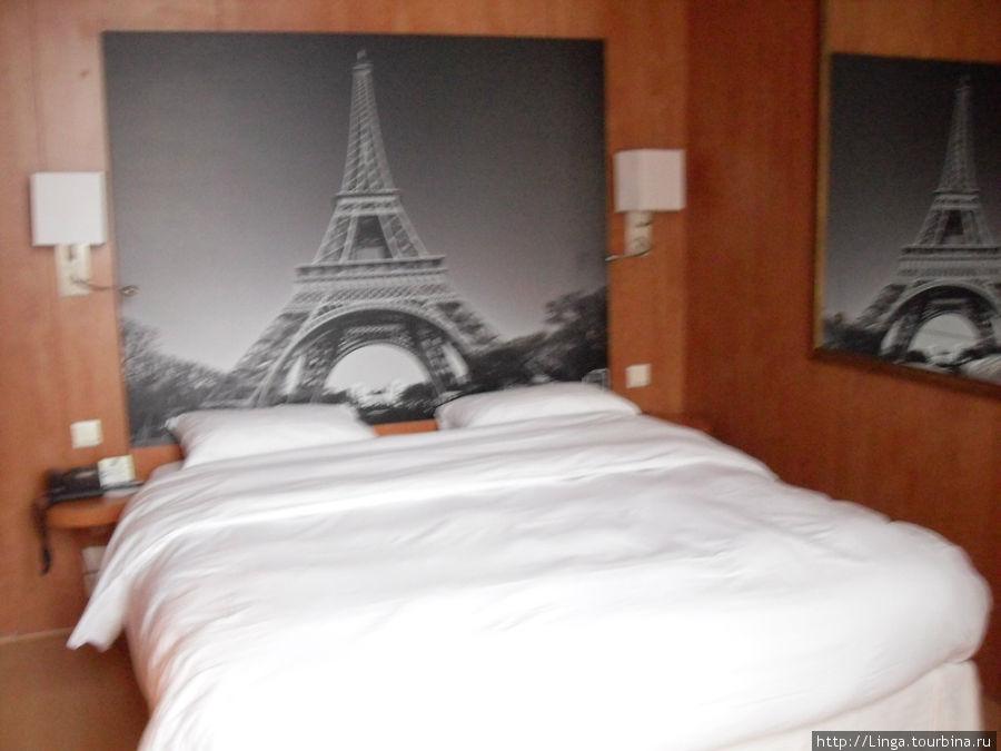 Принт Эйфелевой башни вместо изголовья кровати.