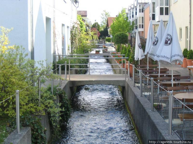 Здесь ручей обретает набережные, многочисленные мостики между домами, по всему берегу — пивные, кафе и пиццерии