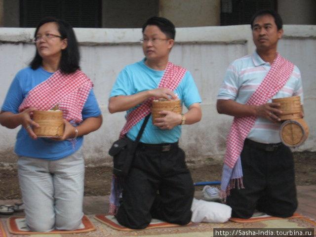 Добродетельные буддисты-миряне садятся вряд вдоль улицы приготовив подношения монахам. По уставу буддийском монахам запрещено прикасаться к деньгам, но они могут получать в качестве милостыни пищу. Поэтому по утрам благочестивые люди раздают монахам горячий рассыпчатый рис.