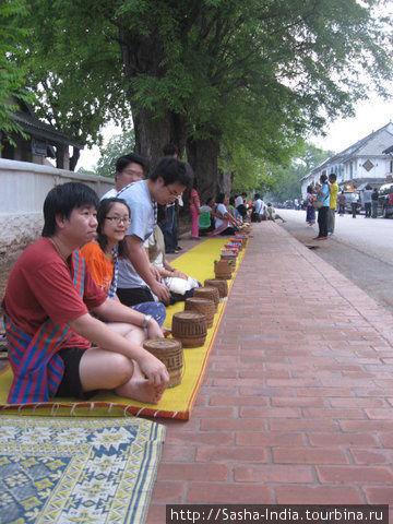 Добродетельные буддисты-миряне садятся вряд вдоль улицы приготовив подношения монахам.