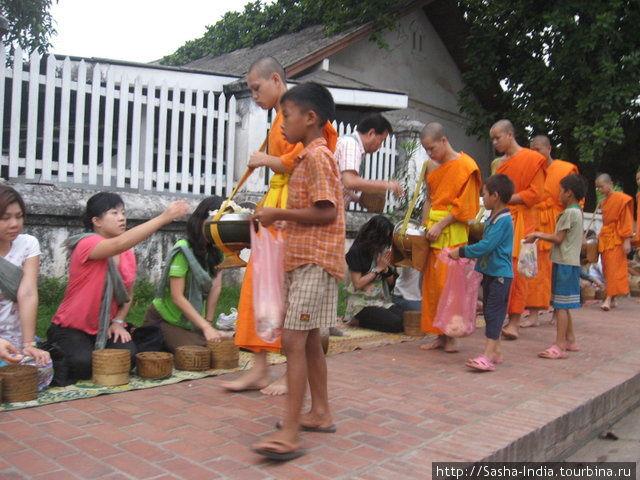 Рядом с монахами крутятся дети из бедных семей с большими пакетами — им тоже перепадает милостыня, но уже из рук монахов, так как обычно монахам жертвуют больше, чем они могут съесть.