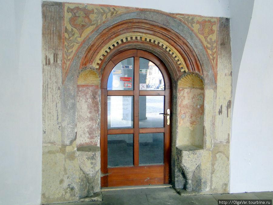 Портал с  эмблемами средневекового мастера Бартоша – колокола и кувшина