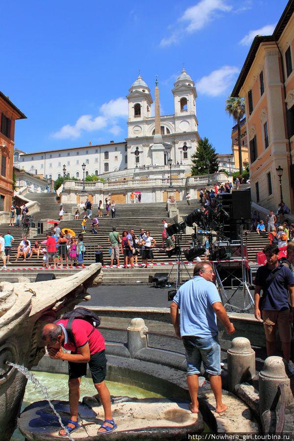 Передний план -люди умываются водой из фонтана Баркачча Средний план — Испанская лестница Задний план — церковь Тринита-деи-Монти