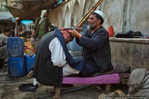 Среди торговых рядов работают уличные парикмахеры.