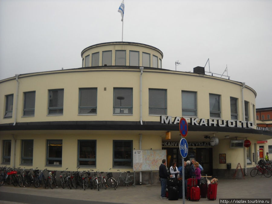 Автовокзал и приезжие; слева от входа виден стенд с картой