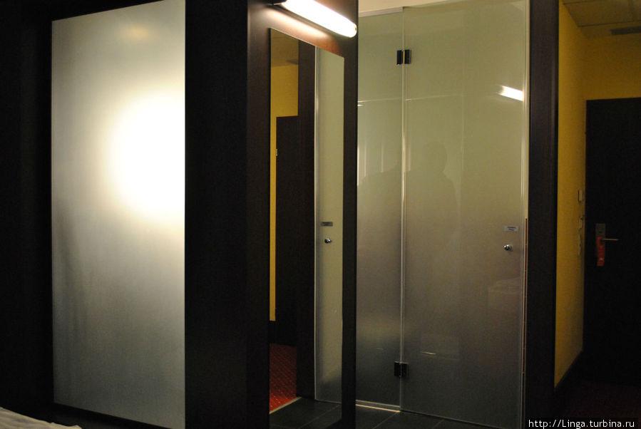 Светящееся матовое стекло слева — это задняя стенка душа, который находится в центре комнаты.