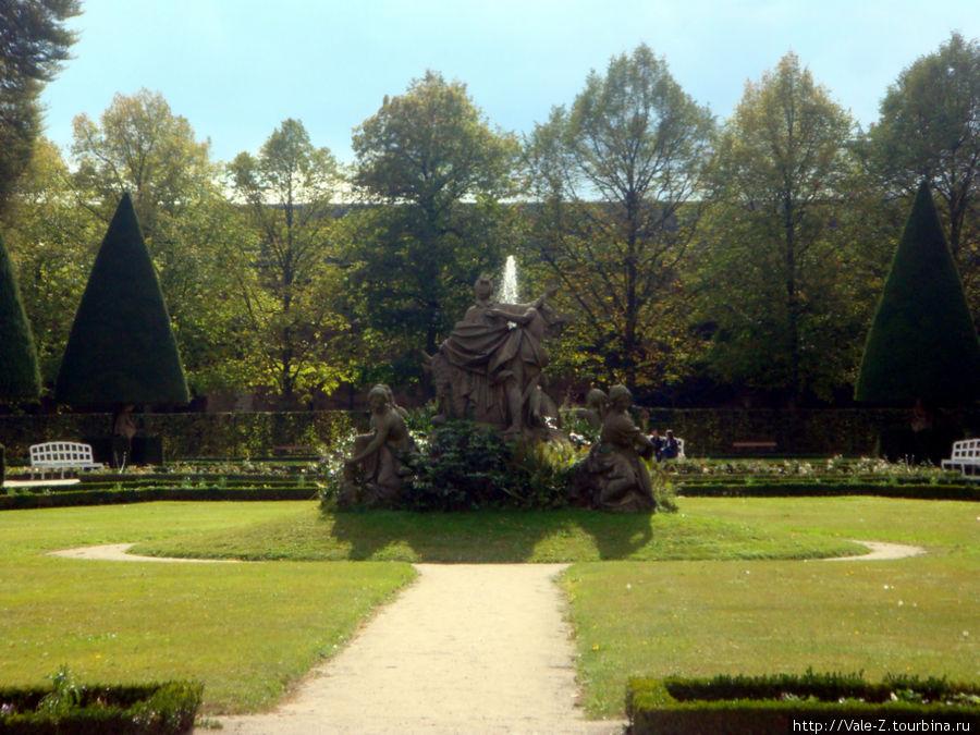 под треугольными кронами деревьев прячутся скульптуры