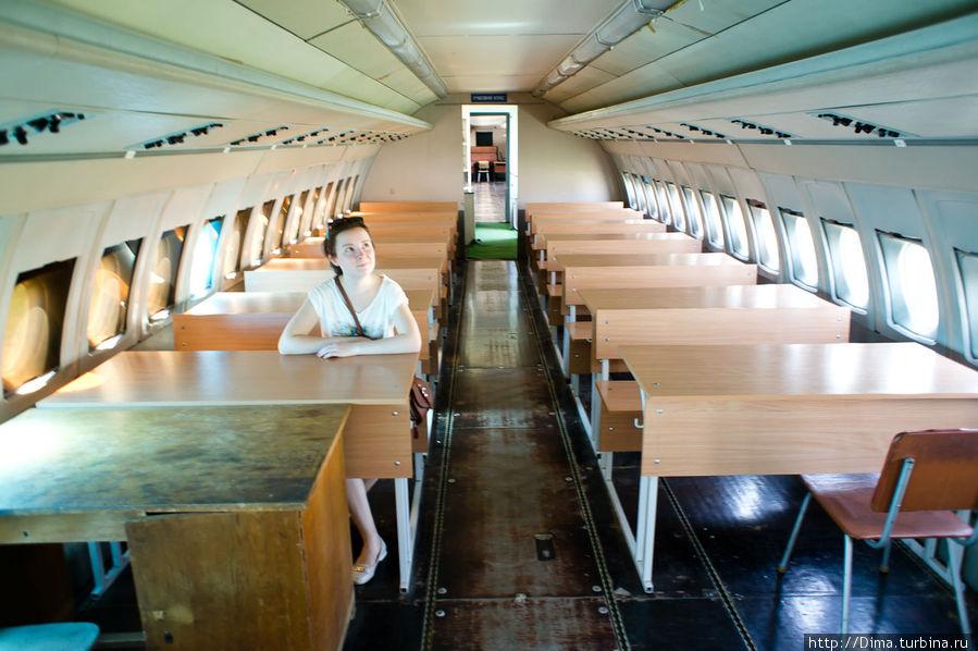 Салон. Вместо сидений — парты. Обратите внимание на то, какие маленькие полки для ручной клади. Они ещё и не закрываются ничем. А салон узкий и низкий. Современные Боинги и Айрбасы гораздо просторнее.