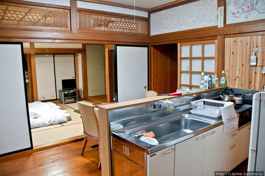 Внутренние помещения от входа: кухня, в глубине — жилая комната 8 татами с уже разложенными футонами.