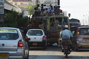 Это городской автобус. Совершенно легально можно ехать на крыше, или зацепившись за бампер. Даже если в салоне много места, многие пассажиры предпочитают забираться на крышу. Дело в том, что проезд вне салона стоит в 2 раза дешевле — 5 рублей, против 10 в внутри. Автобусы водят здесь в основном афганцы — они никого не пропускают и ведут машину крайне агрессивно. Частенько случаются и ДТП, в которых в первую очередь страдают пассажиры