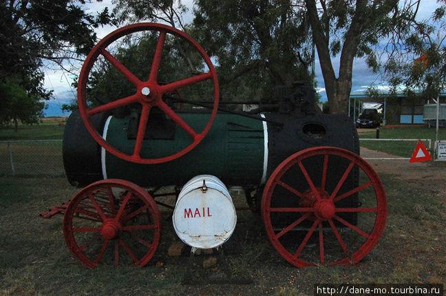 Старая паровая машина и белая бочка, играющая роль почтового ящика
