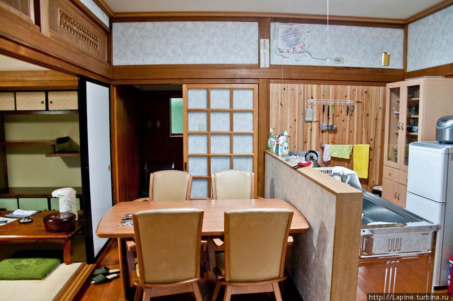 Кухня с обратной стороны, от входа в гостиную. В глубине — раздвижные двери в предбанник онсэнной.