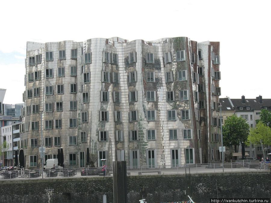 В зеркальных стенах центрального здания, как в алюминиевой банке, отражаются корпуса соседних зданий — белого и красного