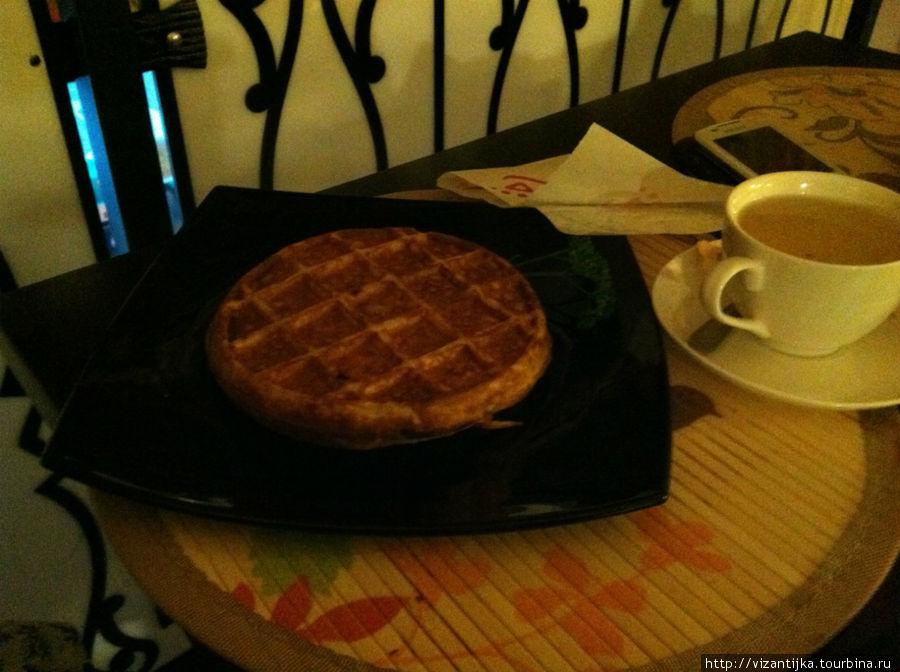 Льёжская вафля на чёрной тарелочке с чашечкой кофе.