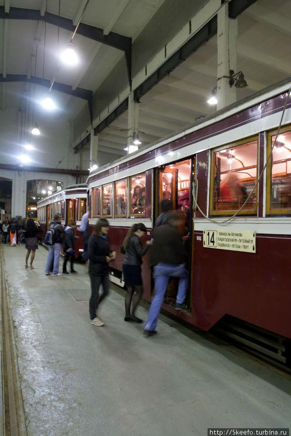 Экскурсанты заходят в трамвай в депо.
