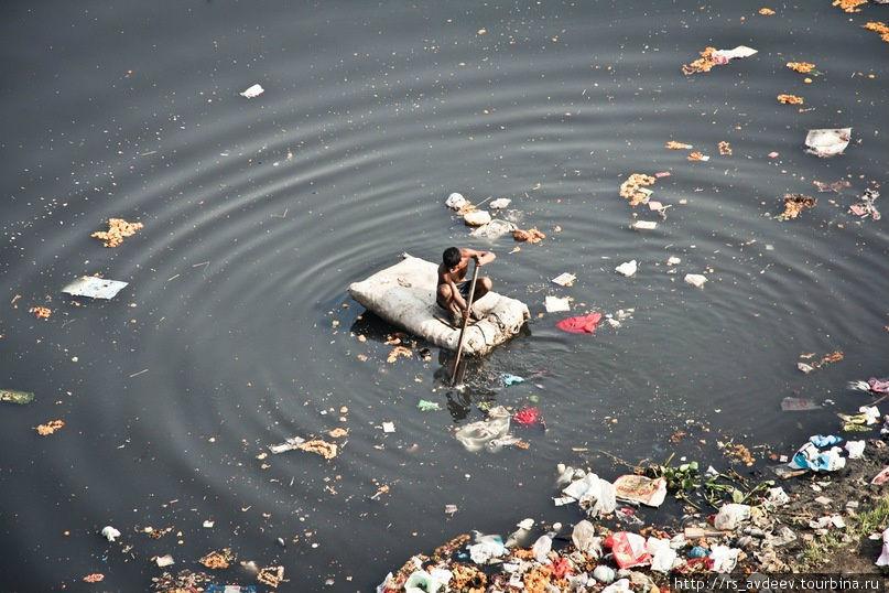 Жители трущоб собирают мусор из реки Джамна в поисках чего нибудь ценного для себя.