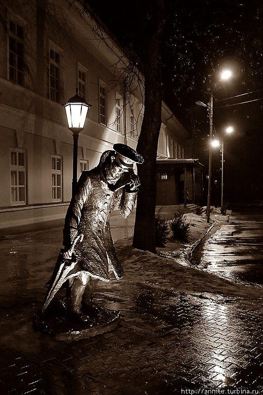 Беликов, пытающийся укрыться от дождя и мокрого снега, да и от самого себя, покидает гимназию поздним вечером. Фото не моё, нашла в интернете, уж очень оно характеризует скульптуру.