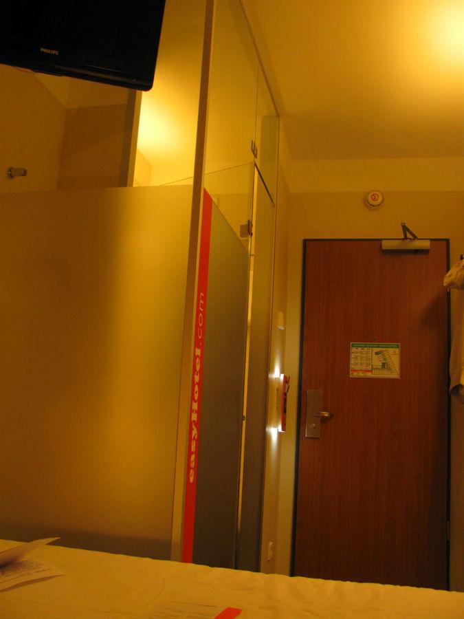 Гостиничный номер: небольшой коридор, санузел за матовым стеклом и кровать.
