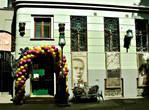На стене большой портрет самого Михаила Афанасьевича, стилизованная под старину скамейка, фонарный столб и панно на стене дома.