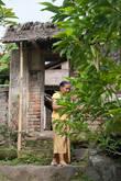 Жительница деревни выносит благовония и подношения богам.