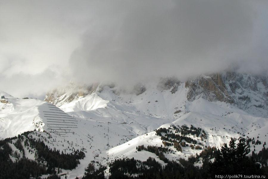 За облаками Sassolungo, 3181 м. Лыжников сюда поднимают из Campitello.