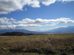 На задем фоне, посреди между двух гор на переднем плане, виднеется гора Фудзи.