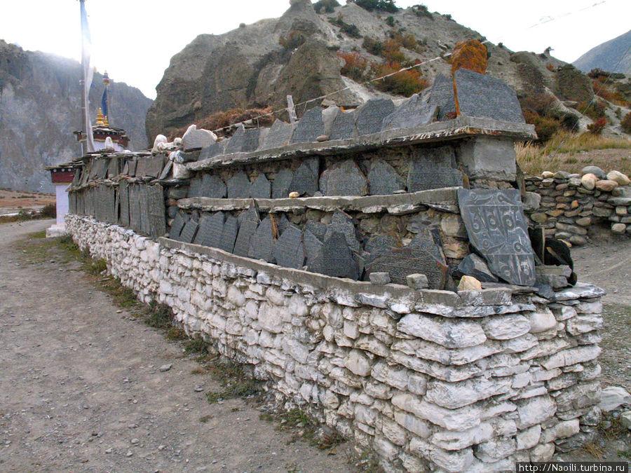 На постаменте рядом со входом выложены камни с вырезанными на них текстами молитв.