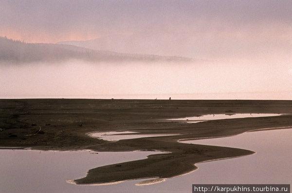 Озеро Накомякен. На южном берегу озера Накомякен, почти напротив долины реки Накта, есть старая рыбацкая изба. Летом она обычно обитаема, хозяева там промышляют рыбалкой. Это очень удобное место для фотосъёмки. Прямо рядом с избой в то время от берега в озеро композиционно простирались песчаные косы причудливых очертаний. Говорят, что теперь там всё изменилось. Впадающая в озеро неподалёку от рыбацкой базы река Нерунгда нанесла столько песка, что береговая линия далеко отодвинулась в озеро. Но солнце летом всё так же опускается к горизонту в понижение долины реки Накта. Это даёт массу возможностей для того, чтобы дождаться интересного момента. Причём такой момент может затянуться на довольно продолжительное время. В июле солнце лишь слегка уходит за горизонт, и закат медленно переходит в рассвет. Лишь бы погода позволила.