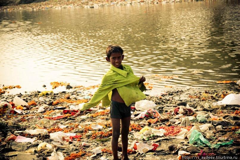 Дети трущоб собирают мусор из реки Джамна в поисках чего нибудь ценного для себя.