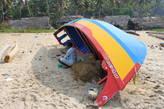 Рыбак спрятался в тени лодки