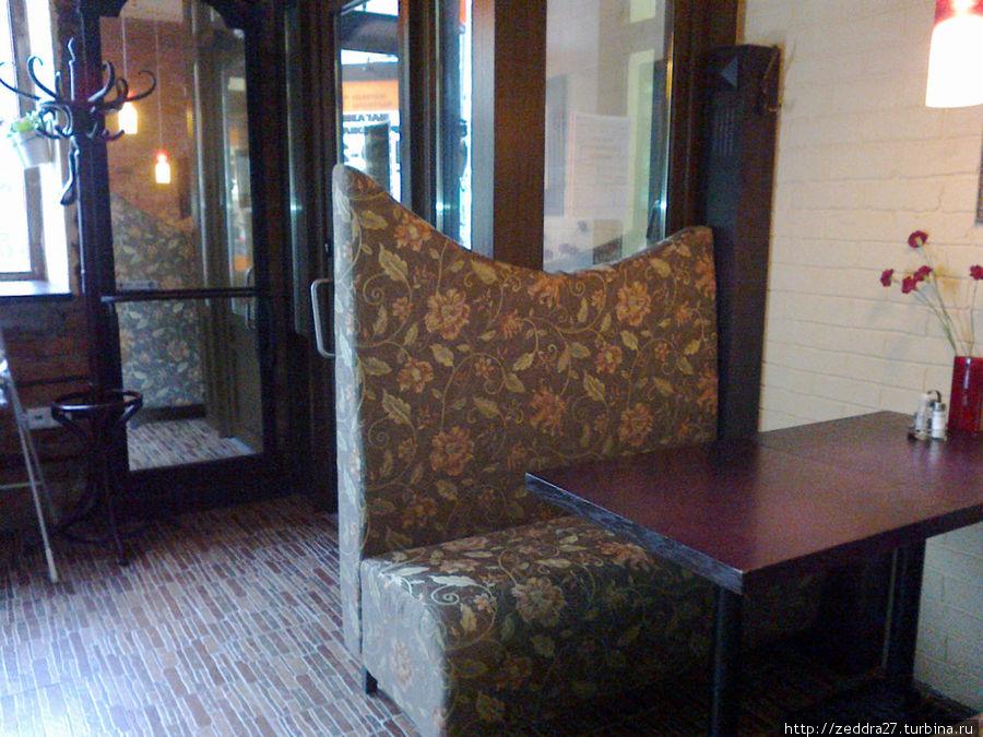 Удобные диваны, старинное зеркало и вешалка у входа, стульчик для грудного ребёнка.