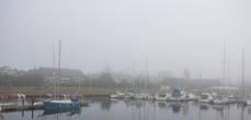 Туманный вид на Истад с пирса яхт-клуба.