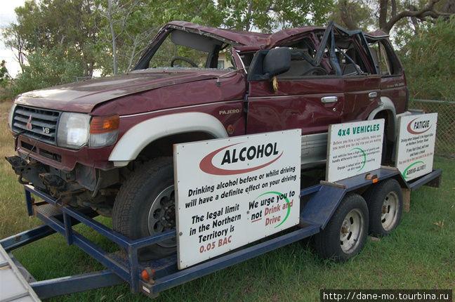 Разбитая машина стоит около забора полицейского участка. На табличках указана информация о технике безопасности при вождении автомобиля.