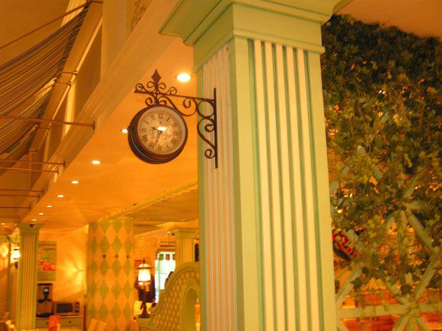 Часы под старину возле касс.
