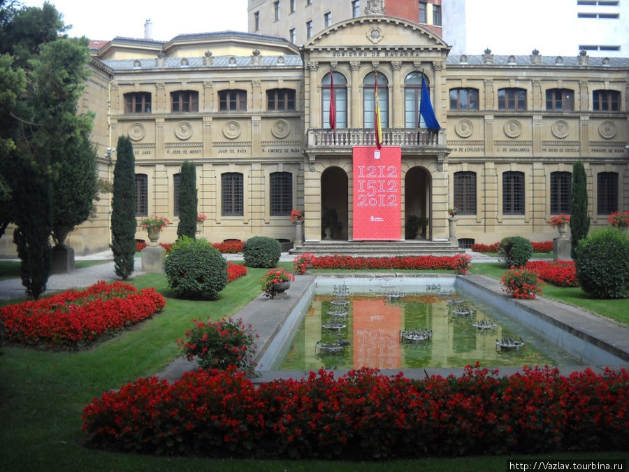 Фасад дворца с прудом и садом