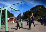 Те, кто нагулялся по горным тропам, развлекаются игрой в баскетбол на спортивной площадке