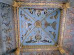 На голубом фоне потолка внутри арки расположились изображения будд, воинов и боевых слонов