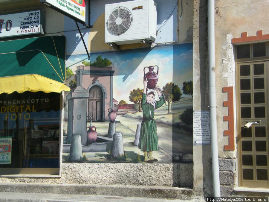 Guspini. Граффити на стенах домов.