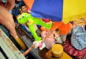 Между тем, самая цветастая часть процессии остается на берегу и разворачивается с каждой минутой все ярче и громче! Продается здесь все — от безумного цвета игрушек и подушек-одеял до только что выловленной в этих самых водах и тщательно зажаренной рыбы, до боли напоминающей своим оскалом знаменитую пиранью!